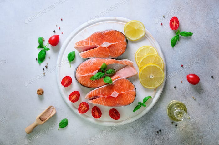 Salmon steaks with lemon, herbs, spices cherry tomatoes on grey concrete background. Healthy diet
