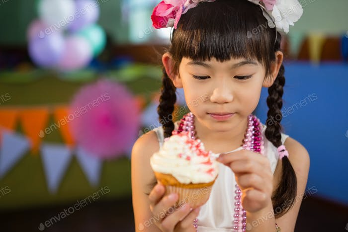 Cute girl decorating cupcake during birthday party