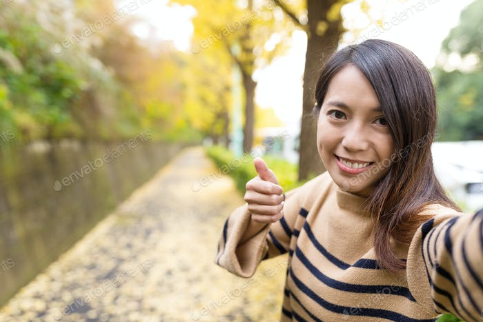 Woman taking selfie and showing thumb up with the road full of ginkgo