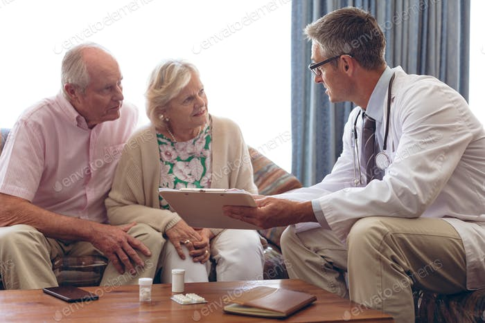 Male doctor interacting with senior Caucasian couple at retirement home