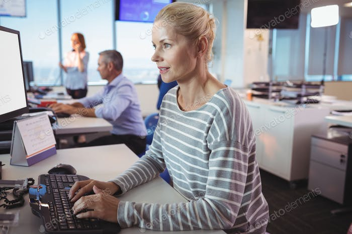 Concentrated businesswoman typing on keyboard at office