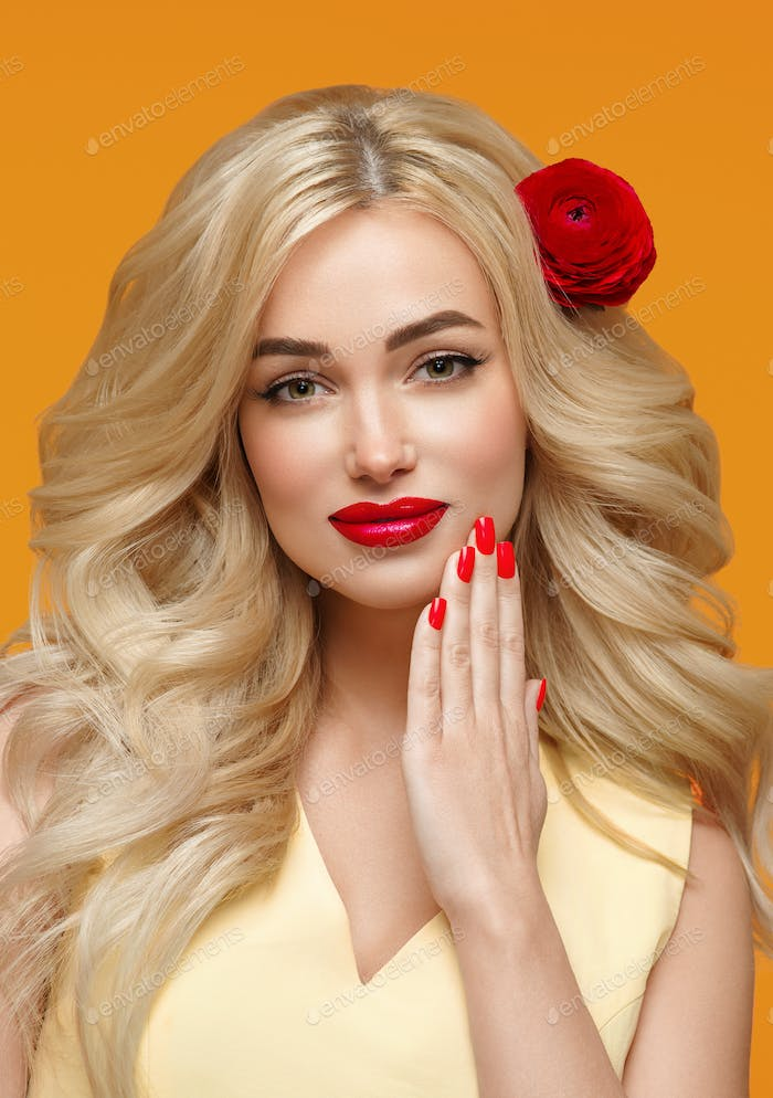 Beauty woman long curly blonde hair flower in hair manicured nails. Trendy colors orange and yellow