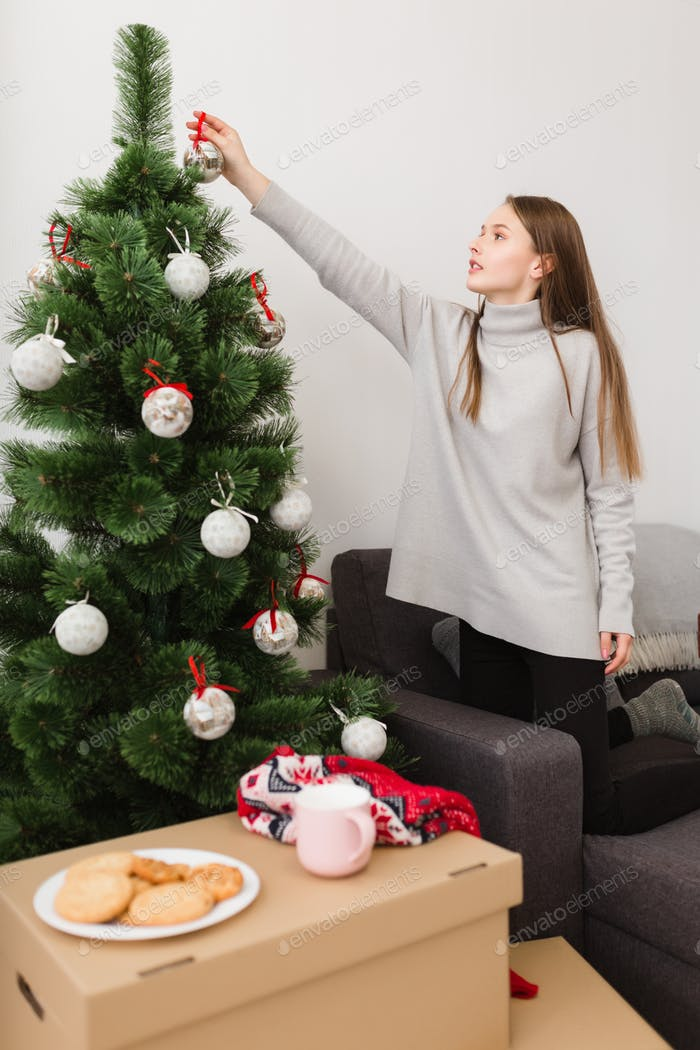 Beautiful girl with brown hair in sweater standing on sofa at home and decorating Christmas tree