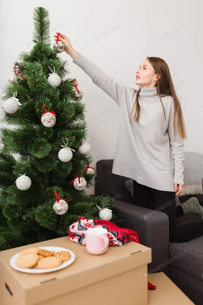 Schönes Mädchen mit braunen Haaren in Pullover stehend auf Sofa zu Hause und Dekoration Weihnachtsbaum