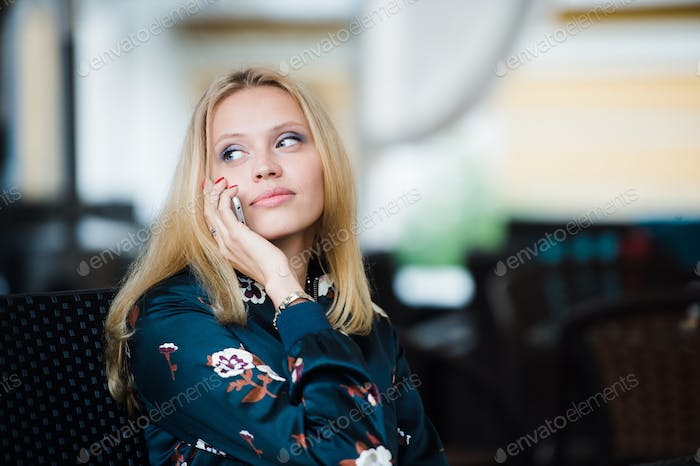 Serious attractive young woman talking on mobile phone in cafe
