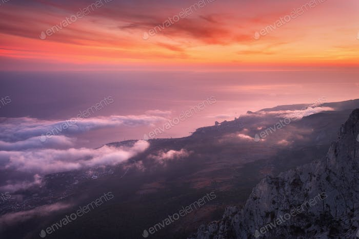 Beautiful landscape with sea, colorful sunset and low clouds