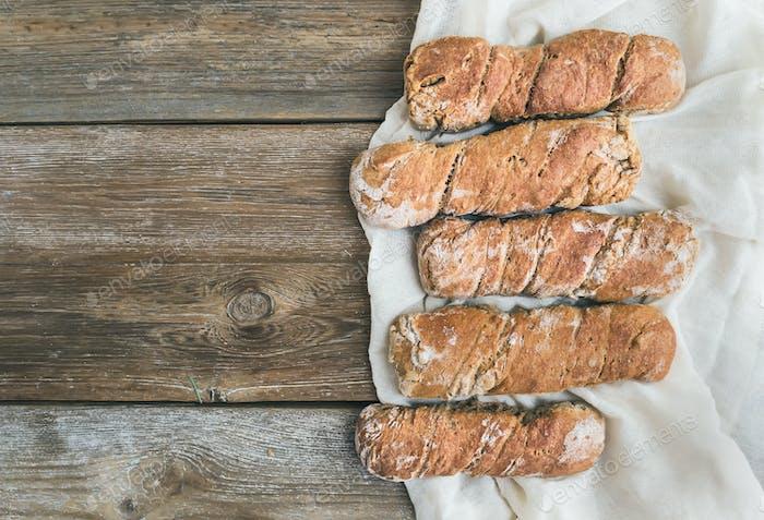 Freshly baked rustic  village bread (baguettes) set on rough woo