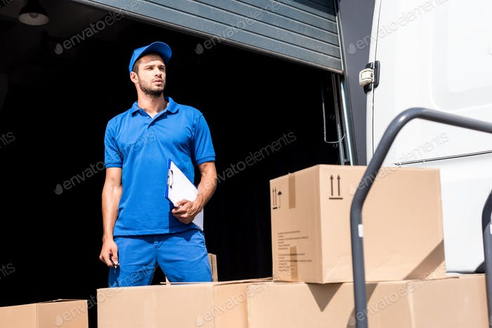 delivery man with clipboard next to warehouse