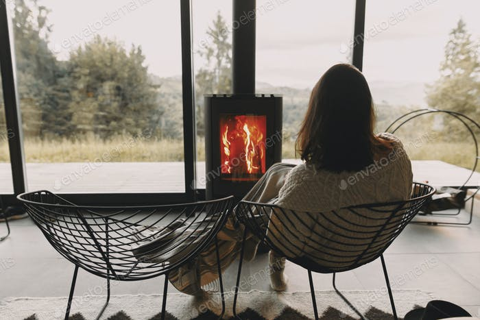 Stylish woman in sweater and hat warming up at modern black fireplace with view on mountains