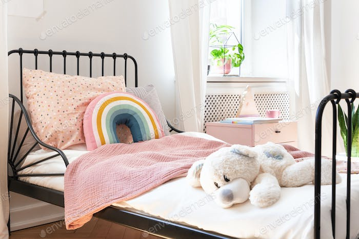 Plush toy, rainbow pillow and pink blanket on kid's bed in white