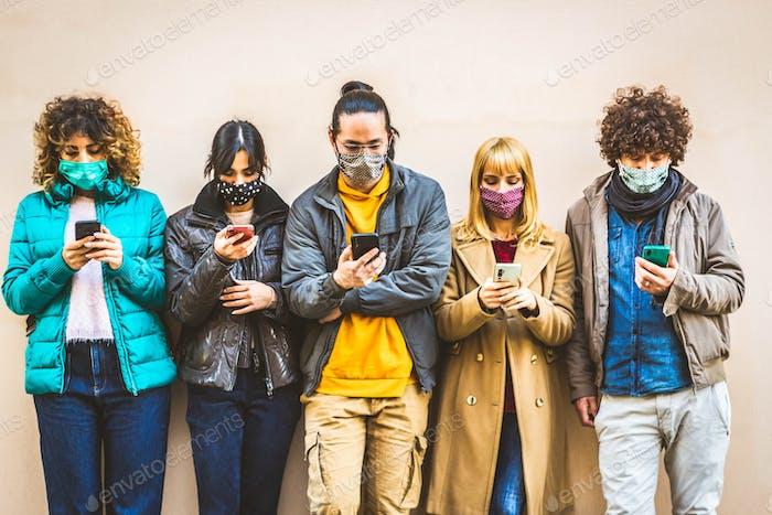 Grupo de jóvenes cubiertos por máscaras faciales usando un dispositivo móvil