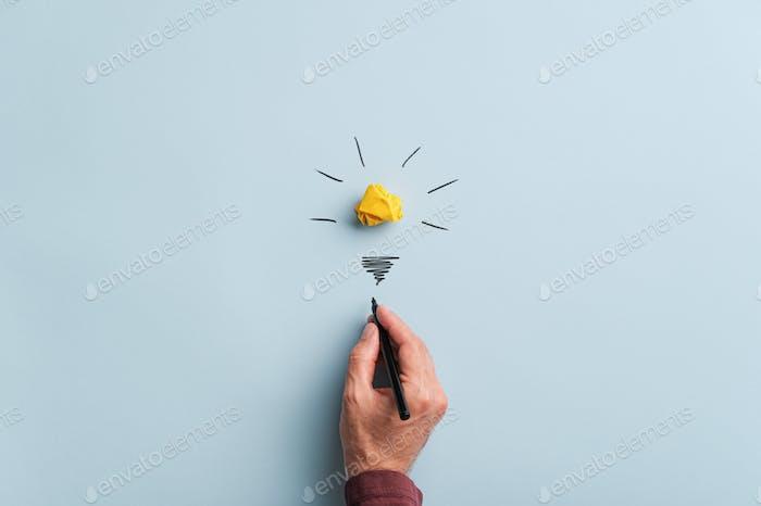 Male hand drawing a light bulb
