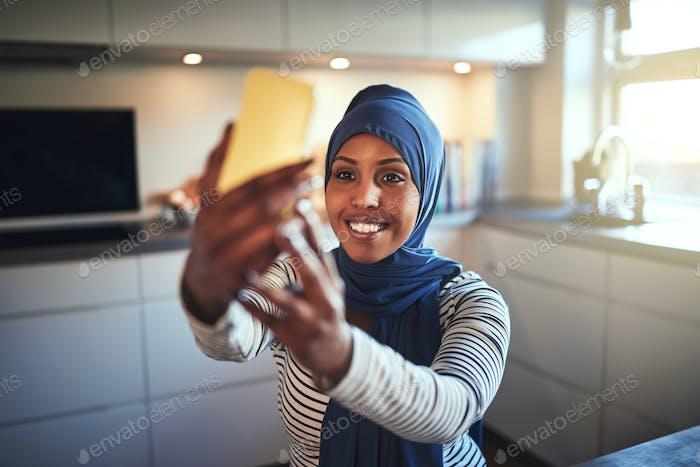 Lächelnd junge arabische Frau nehmen selfies in ihre Küche
