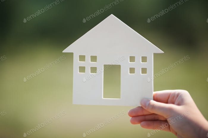 Hand holding house model outdoor
