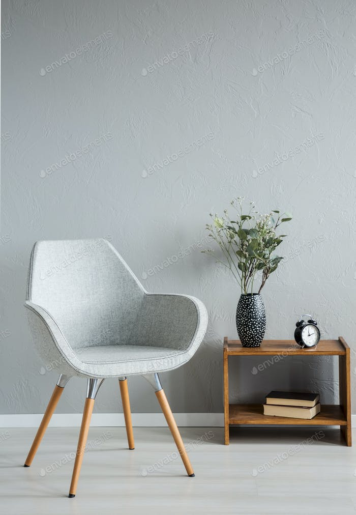 Stylish grey chair next to cabinet with vase and flowers in mode