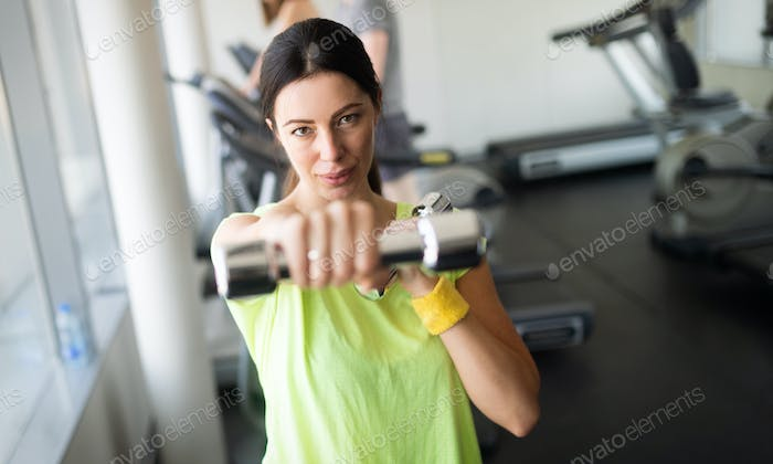 Happy fit woman exercising in a gym to stay healthy