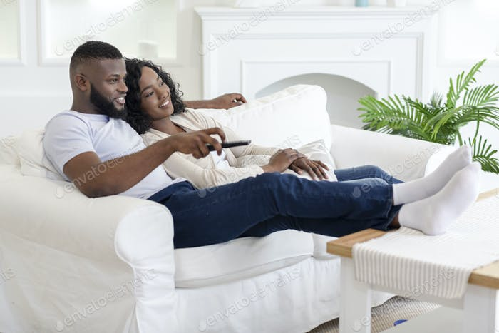 Black couple relaxing on couch at home and watching tv