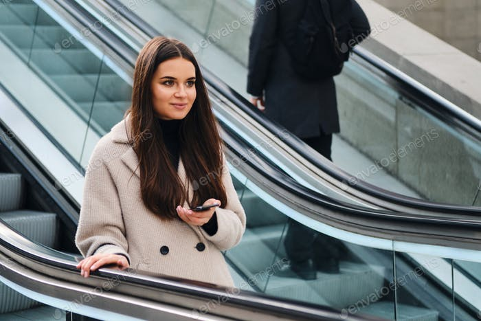 Pretty smiling brunette girl with cellphone on escalator