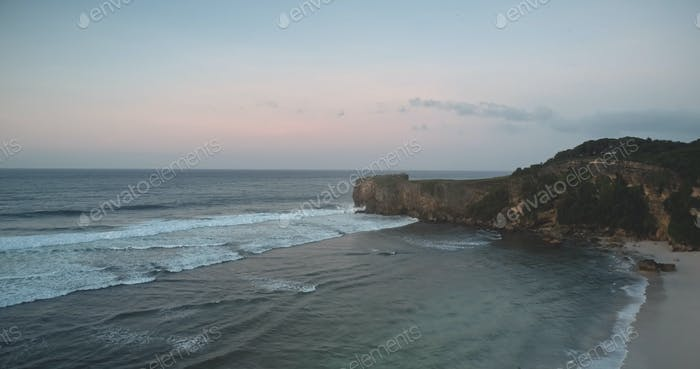 Rock coast at sand beach washed by ocean bay waves aerial view. Nobody tropical Indonesia landscape