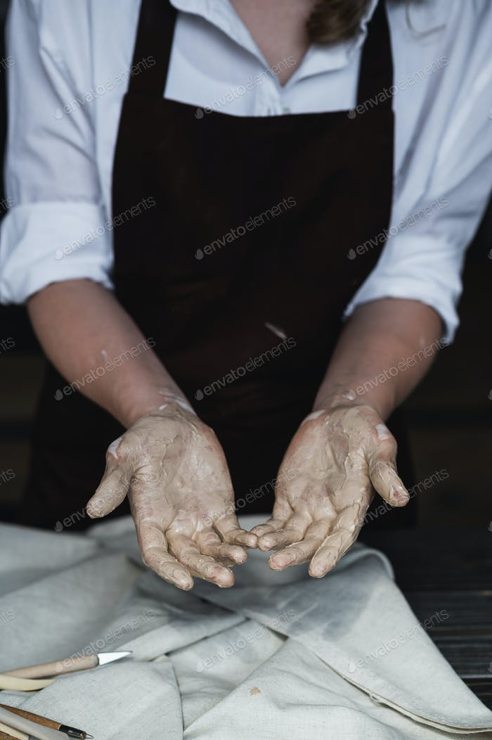 Wet hands covered with gray clay of potter