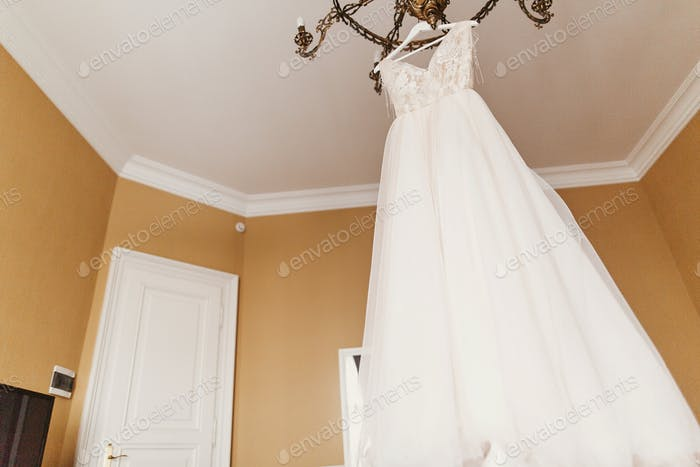 Modern wedding gown hanging on chandelier in room