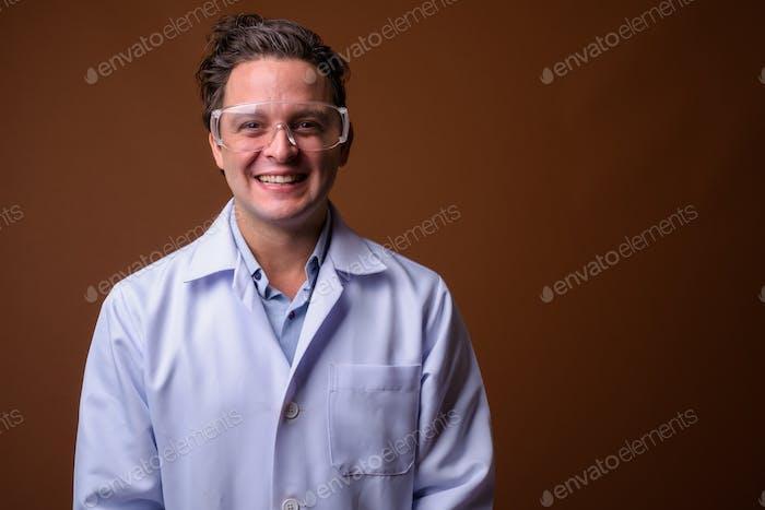 Italienischer Mann Arzt trägt Schutzbrille gegen braunen Rücken