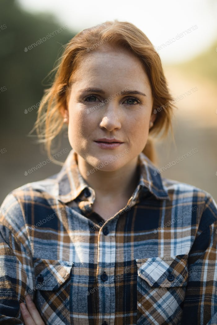 Portrait of beautiful young woman at farm