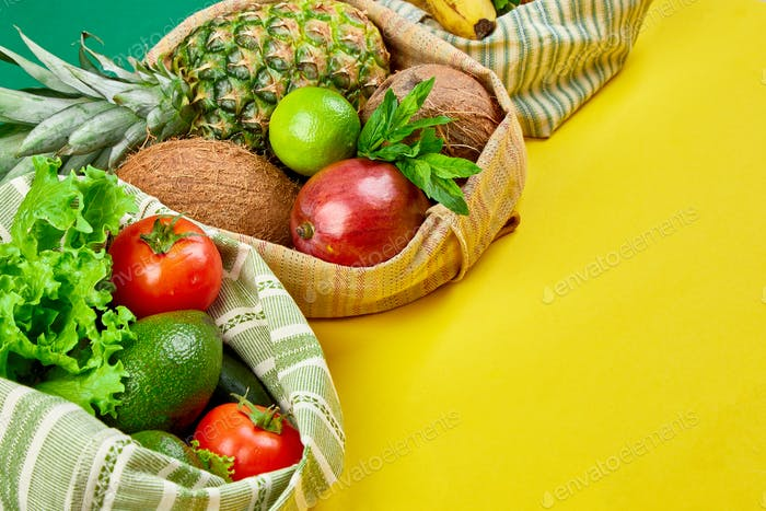 Flat lay of eco friendly grocery shopping cotton bags with organic fruits and vegetable