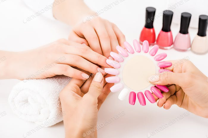 Partial view of manicurist holding pink nail polish palette