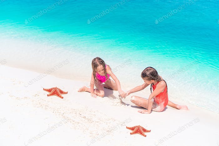 Adorable little girls with starfish on white empty beach