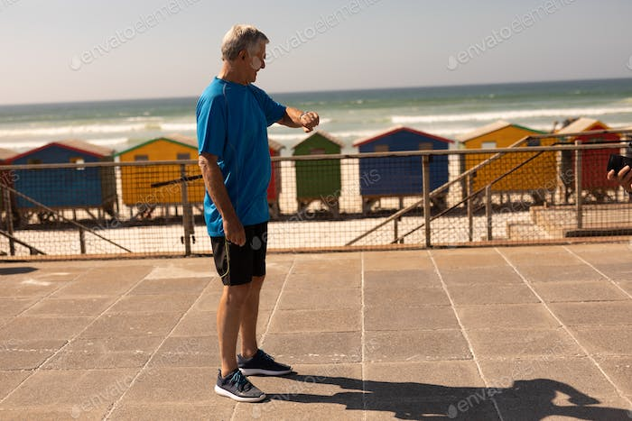 Side view of active senior man checking time on smartwatch on promenade at beach