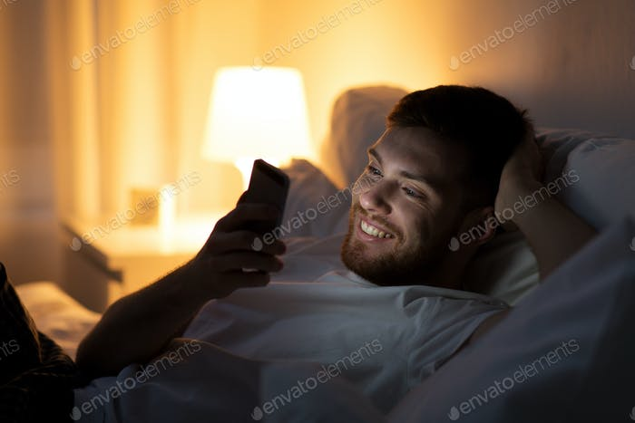 happy young man with smartphone in bed at night