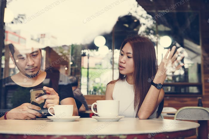Couple using a phone at a cafe