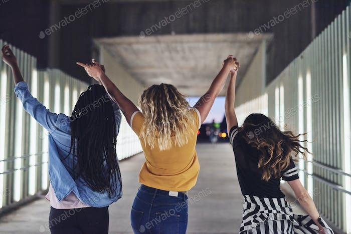 Carefree young women holding hands together at night