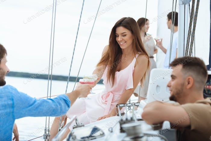 Glückliche lächelnde Frau trinken Wodka Cocktails auf Boot-Party im Freien, fröhlich und glücklich