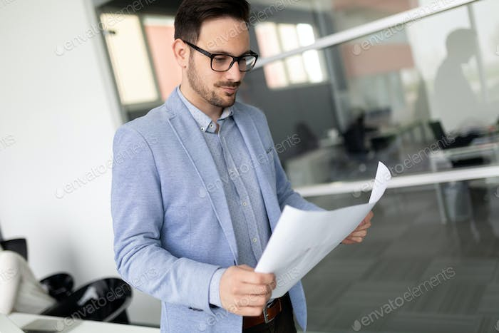 Portrait of young businessman, successful entrepreneur working day in office