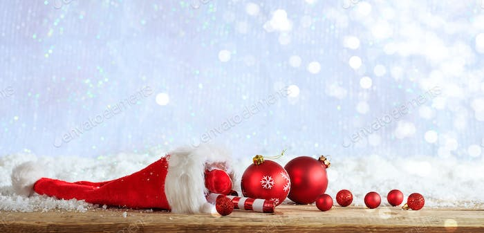 Christmas ornaments and santa hat on wooden snowy background