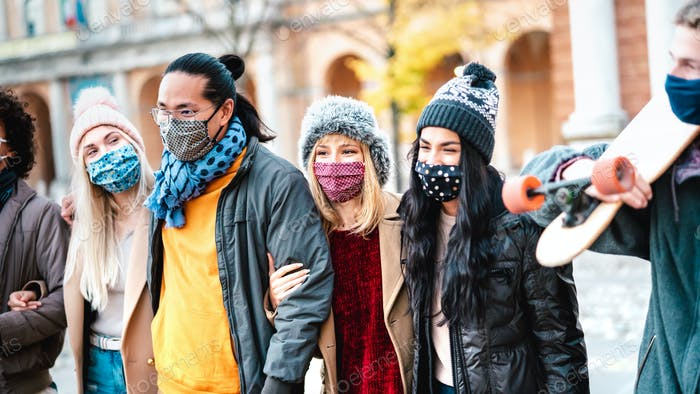 Happy friends walking at city center with face mask