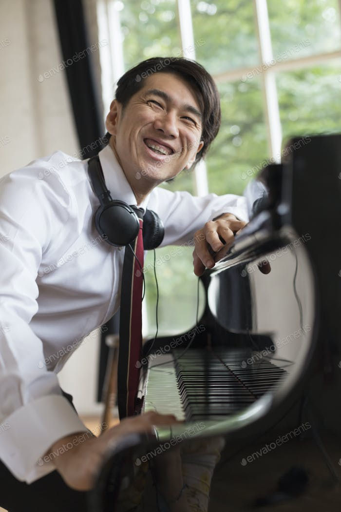 Young smiling man sitting at a grand piano in a rehearsal studio, wearing headphones round his neck.