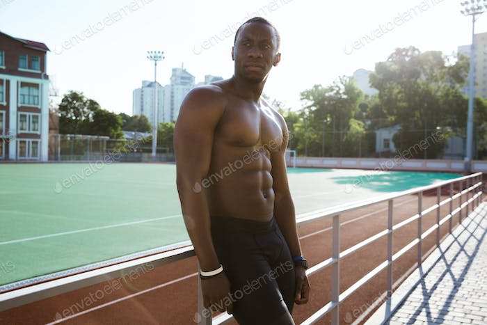 Young tired african athlete man resting