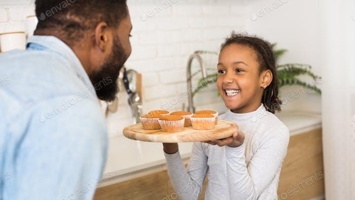 glücklich afro Mädchen zeigen Ihr Vater frisch gebackene Muffins