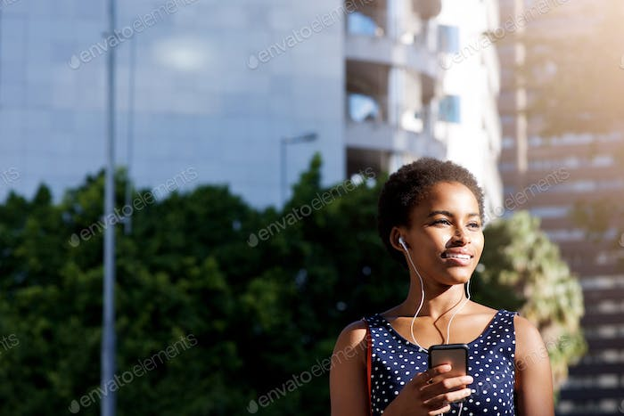 beautiful black woman smiling with earphones and cellphone in city
