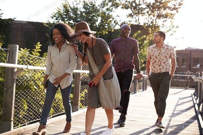 Gruppe von Freunden Spaziergang entlang Brücke in städtischer Umgebung