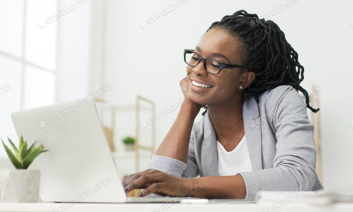 Cheerful Afro Office Girl Using Laptop At Workplace