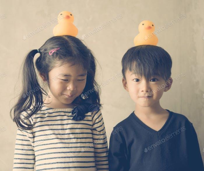 Japanische Kinder mit Gummi-Enten auf ihren Köpfen