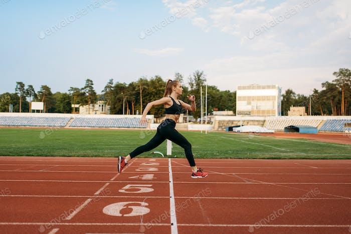 Female runner crosses finish line on stadium