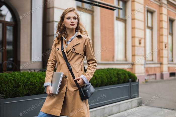 Beautiful attractive woman in trench coat with little black cros