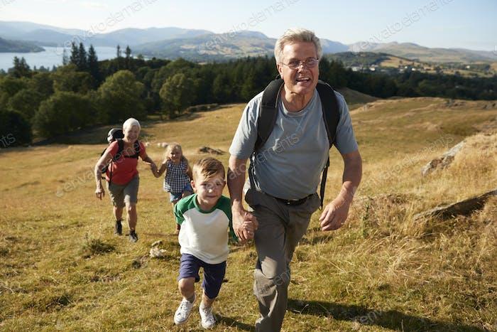 Grandparents With Grandchildren Climbing Hill On Hike