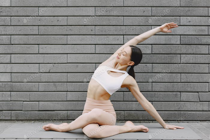 Woman practicing advanced yoga against a dark urban wall