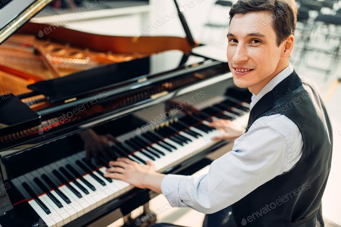 Male pianist poses at the black grand piano